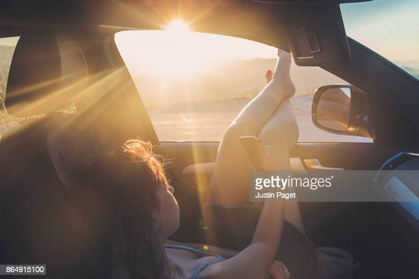 Teenage Girl using phone in car at sunset
