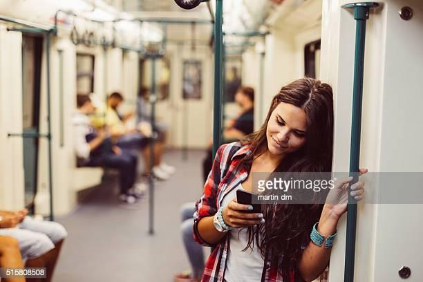 Teenage girl using phone in the subway train