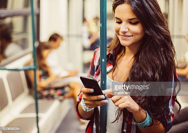 Teenage girl using phone in the subway train