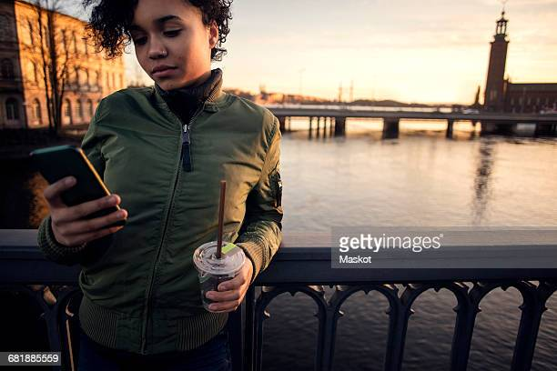 Teenage girl using phone while having drink by railing against canal in city