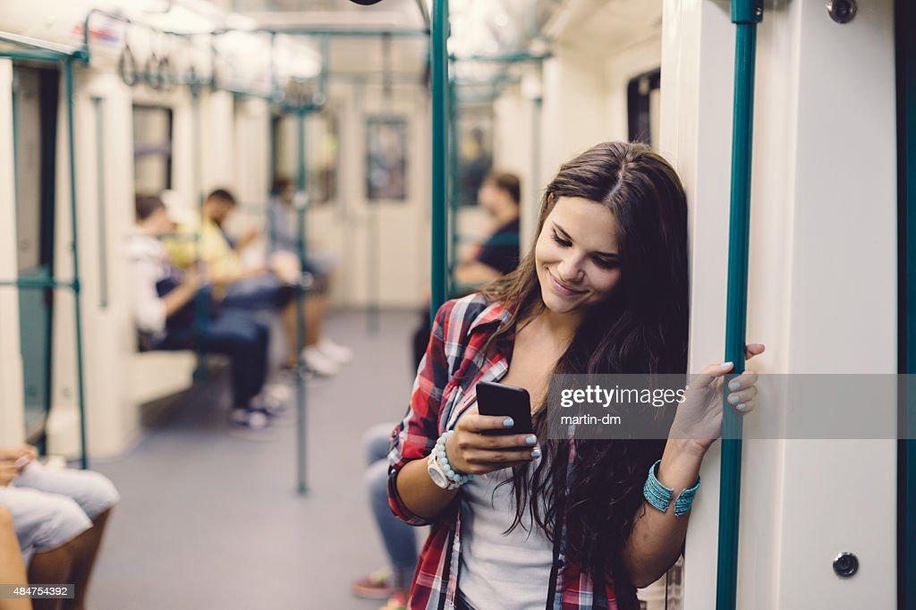 を使用して 10 代の少女の電話で、ご旅行中の地下鉄 : ストックフォト