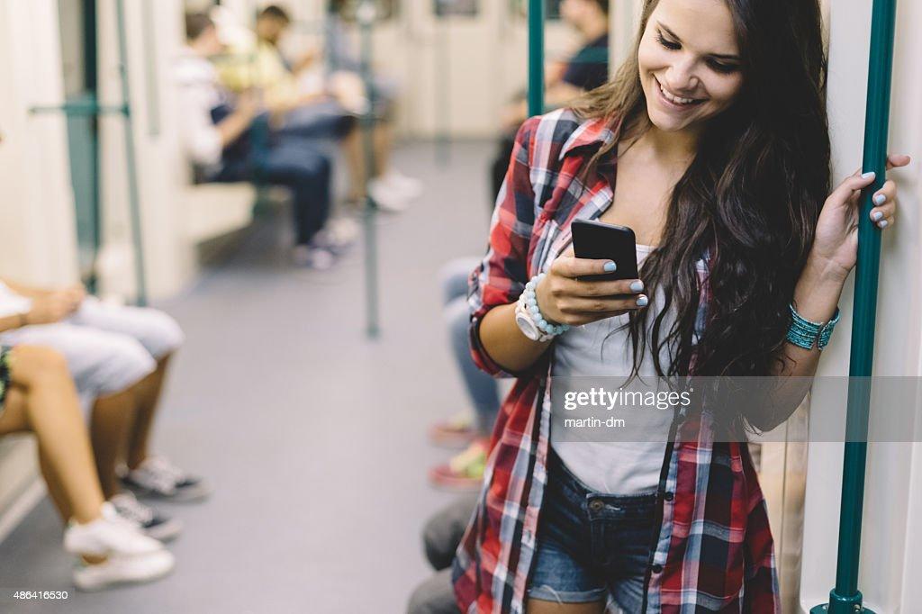 Teenager-Mädchen mit Telefon, während Reisen in die U-Bahn : Stock-Foto