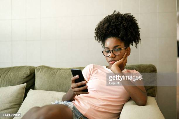 teenage girl using smart phone on couch - boredom stock pictures, royalty-free photos & images