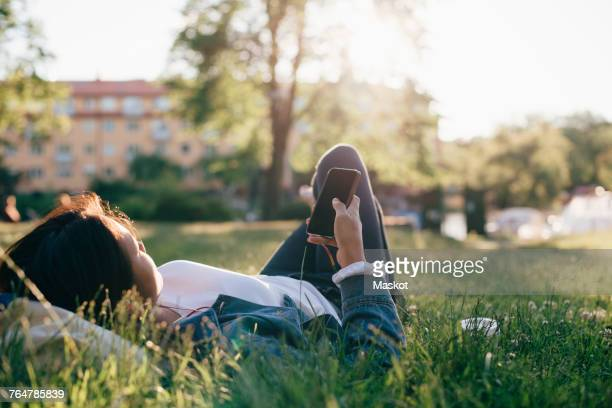 teenage girl using smart phone while lying on grass - one teenage girl only stock pictures, royalty-free photos & images