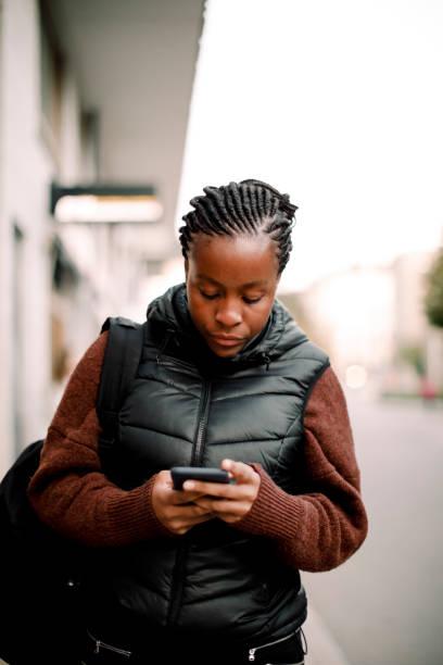 Teenage girl using smart phone while walking on footpath in city