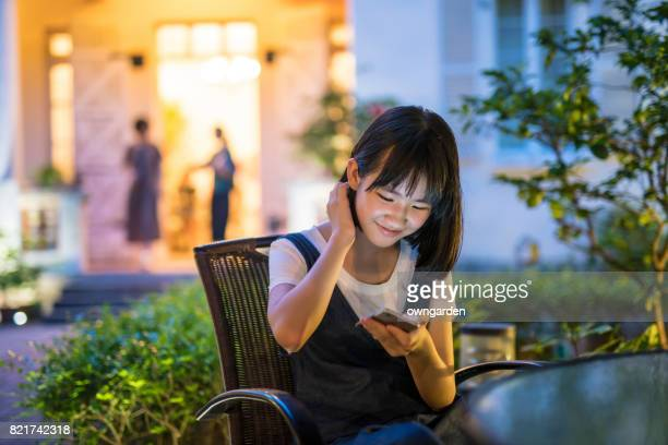 Teenage girl using smartphone in the garden
