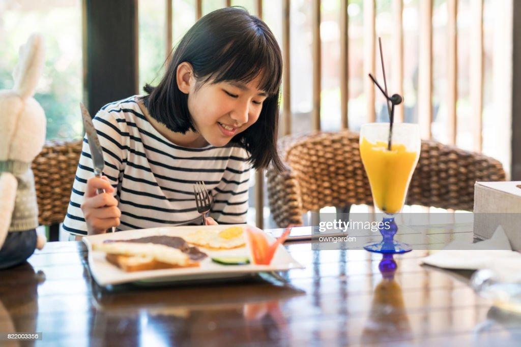 Teenage girl using smartphone in the restaurant : Stock Photo
