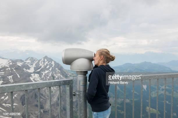 Teenage girl using the telescope, Suspension Bridge. Col Du Pillon. Diablerets. Gstaad. Switzerland