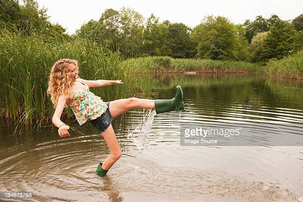 Teenage girl wading into the middle of a lake with over-flowing wellies
