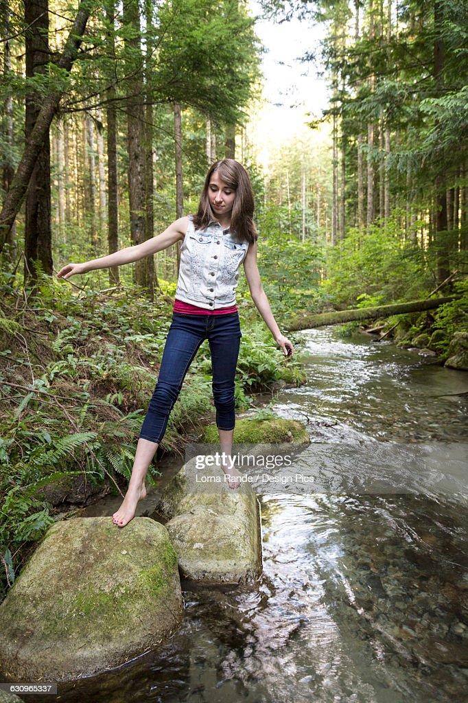 Teenage Girl Walking Barefoot Over Rocks In A Stream Stock