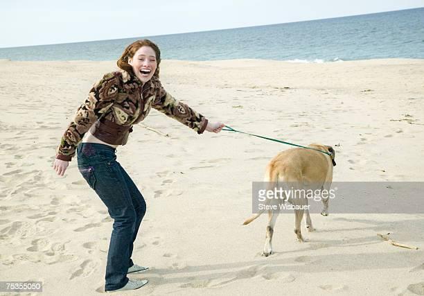 Teenage girl (16-18) walking dog on beach, smiling, portrait