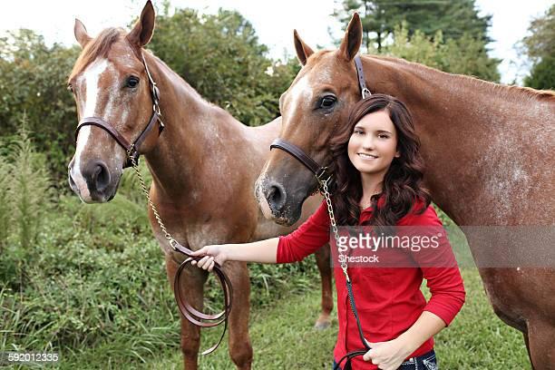 Teenage Girl Walking Horses In Rural Field