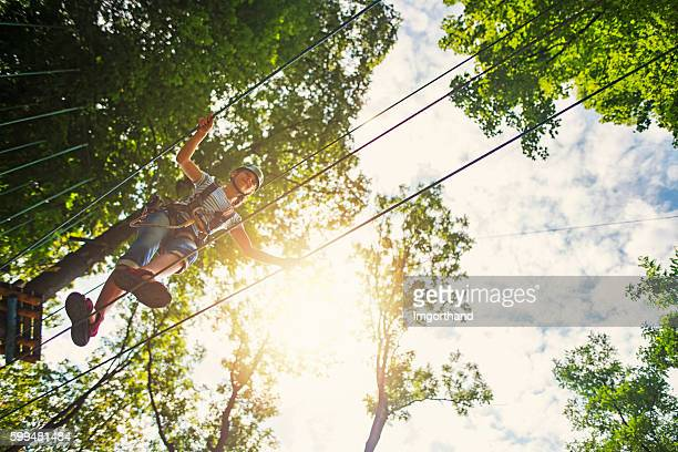 teenage girl walking on a line in adventure park - high up stock photos and pictures