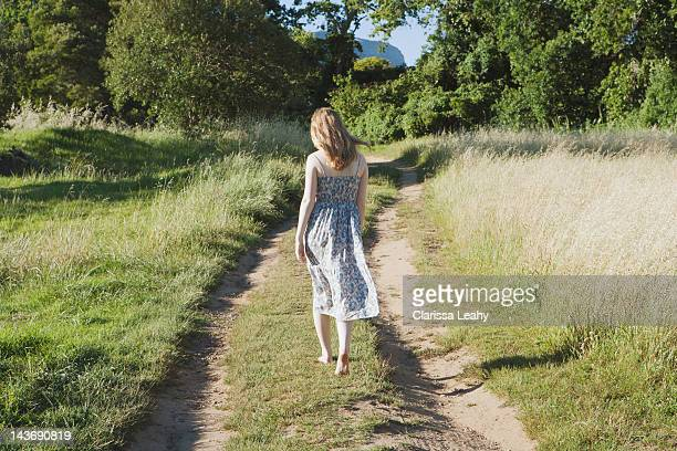 teenage girl walking on dirt path - donne bionde scalze foto e immagini stock