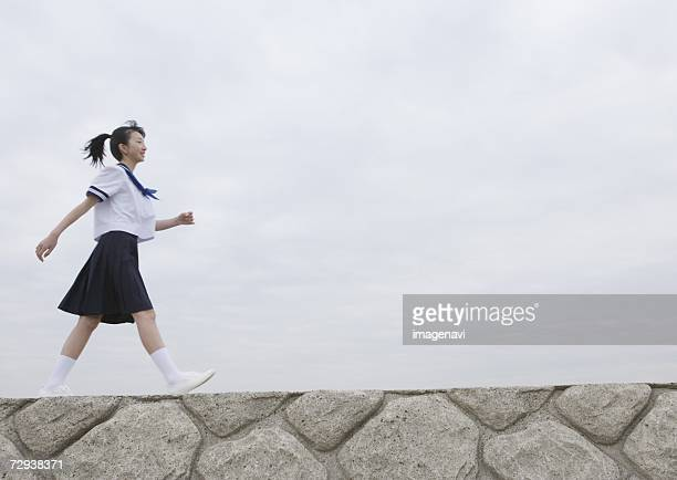 Teenage girl walking on pier