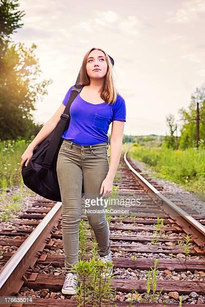 Teenage girl walking on railroad track with guitar