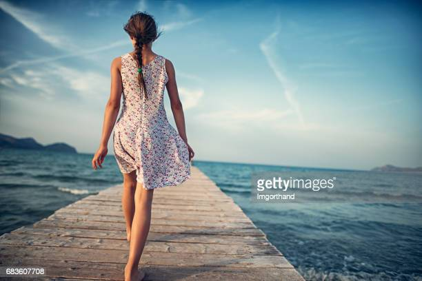 Teenage girl walking on sea pier