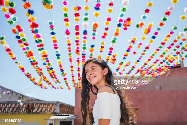 teenage girl walking on street decorated for festival - tradition stock pictures, royalty-free photos & images