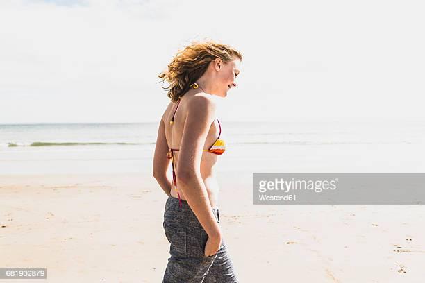 Teenage girl walking on the beach