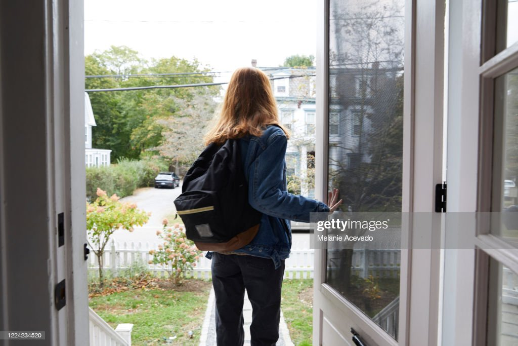 Teenage girl walking out the front door of her house. Back view of her leaving the house. She is on her way to school, wearing a back pack and holding the door open. : Photo