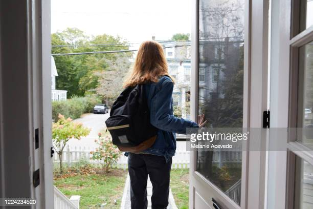 teenage girl walking out the front door of her house. back view of her leaving the house. she is on her way to school, wearing a back pack and holding the door open. - leaving fotografías e imágenes de stock