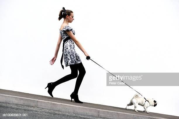 Teenage girl (14-15) walking with pug dog, side view