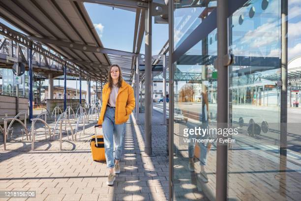 teenage girl walking with suitcase on street in city - val thoermer stock-fotos und bilder