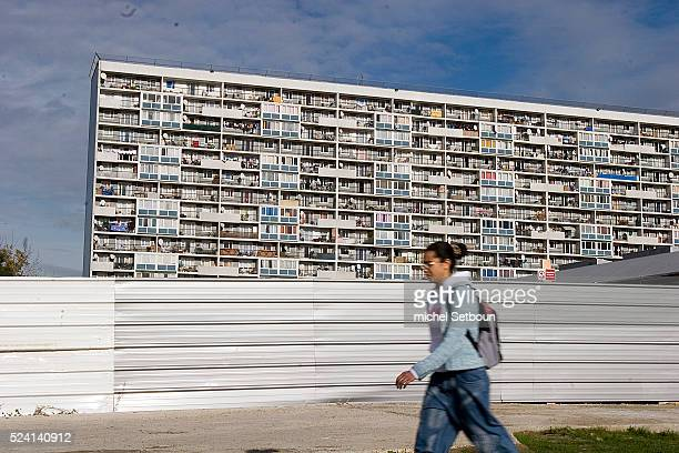 A teenage girl walks past a tower block in la Cite des 4000 in La Courneuve in the Paris suburbs