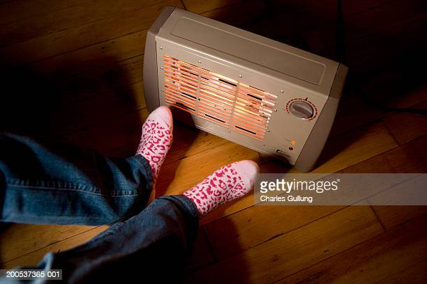 Teenage girl (14-16) warming feet beside electric heater, low section