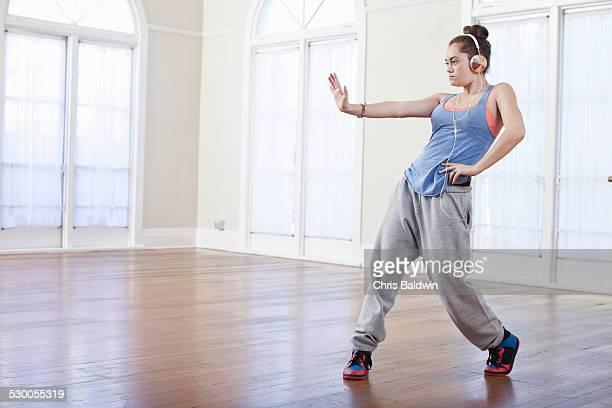 Teenage girl warming up with alternative dance in ballet school