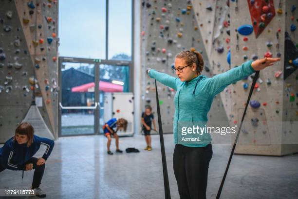 teenage girl warming up with resistance bands at climbing gym - warming up stock pictures, royalty-free photos & images