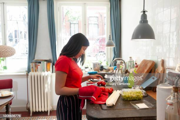 Teenage girl washing and drying tomatoes