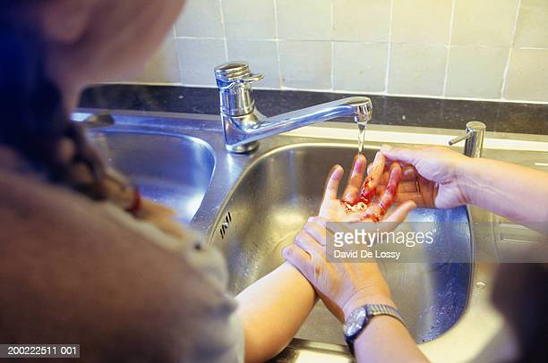 teenage girl (14-15) washing blood from hands in kitchen sink - blood in sink stock pictures, royalty-free photos & images