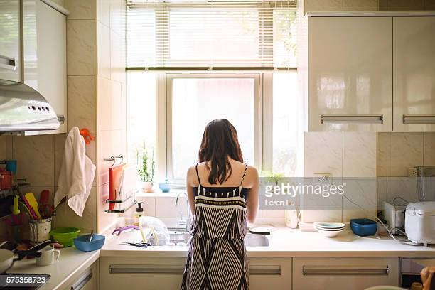 Teenage girl washing dishes in kitchen