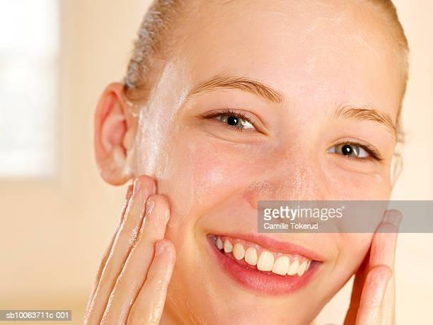 Teenage girl (13-14) washing face, smiling, portrait, close-up