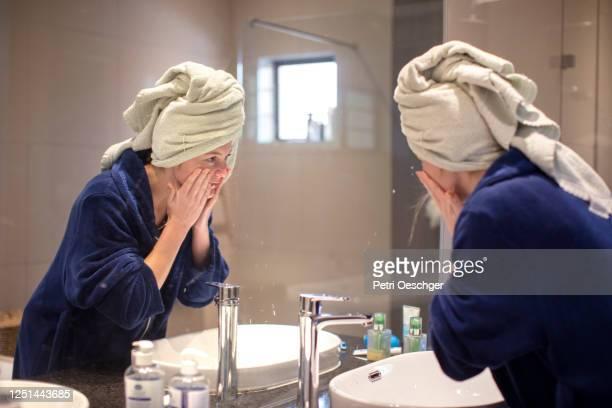 ein teenager-mädchen waschen ihr gesicht nach dem duschen. - hautausschlag stock-fotos und bilder