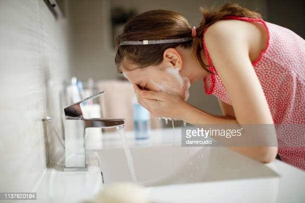 teenage girl washing her face with water - routine stock pictures, royalty-free photos & images