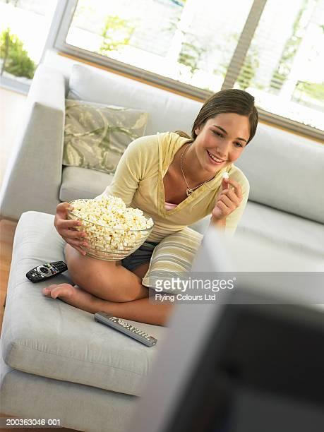 Teenage girl (14-16) watching television, holding popcorn, smiling