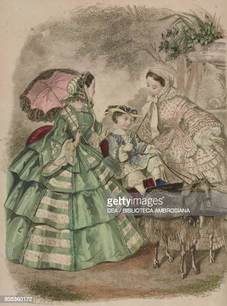 Teenage girl wearing a green taffeta dress holding an umbrella child wearing a lightcoloured dress sitting on a cart pulled by a goat teenage girl...