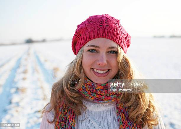 Teenage girl wearing a hat and a scarf, stand on a snow-covered lawn