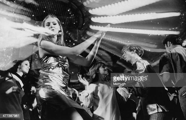 A teenage girl wearing a metallic dress dancing at a discotheque September 1974