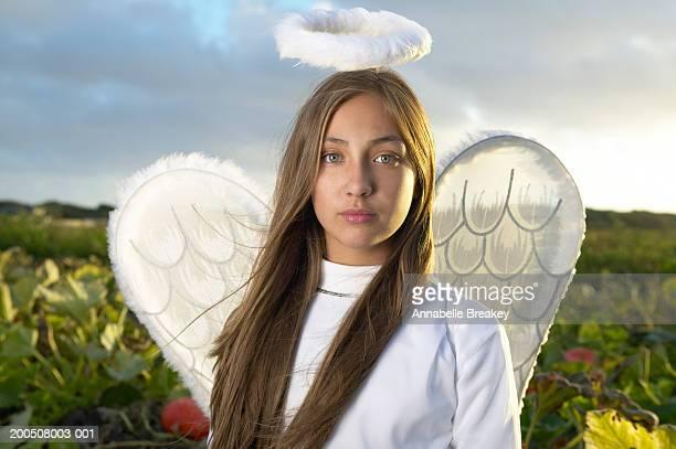 Teenage girl (12-14) wearing angel costume in pumpkin patch