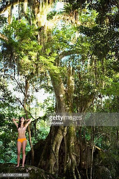 Teenage girl (16-17) wearing bikini, standing on boulder in tropical forest