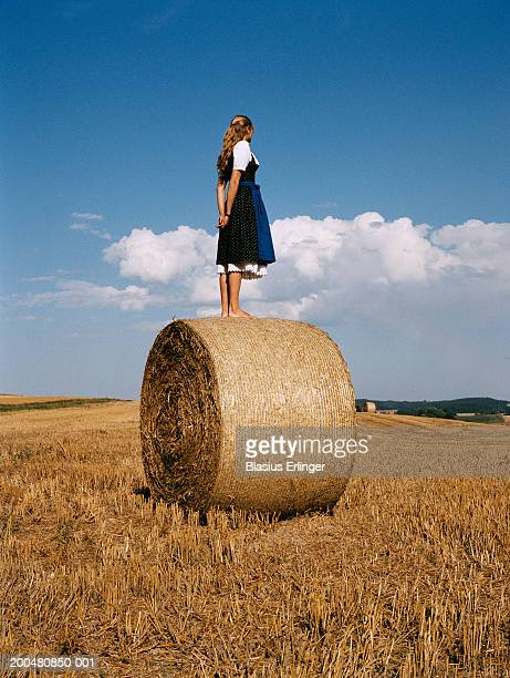 teenage girl (16-18) wearing dirndl, standing on bale of hay - bavaria stock pictures, royalty-free photos & images