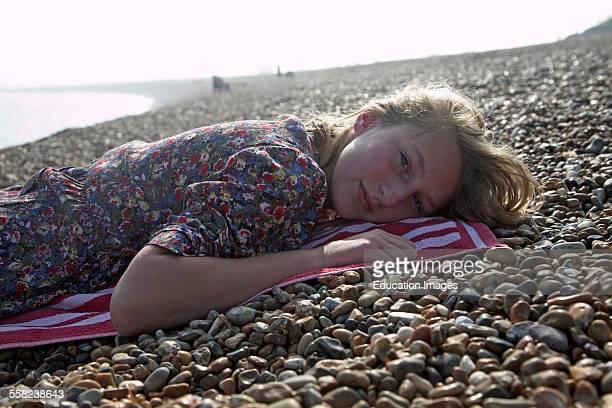 Teenage girl wearing floral dress lies on shingle beach