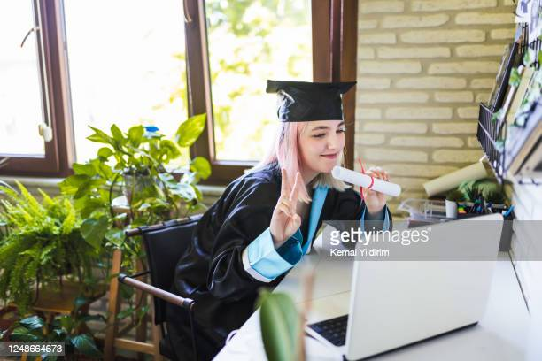 teenage girl wearing graduation gown and cap greeting her family on video call - graduation stock pictures, royalty-free photos & images