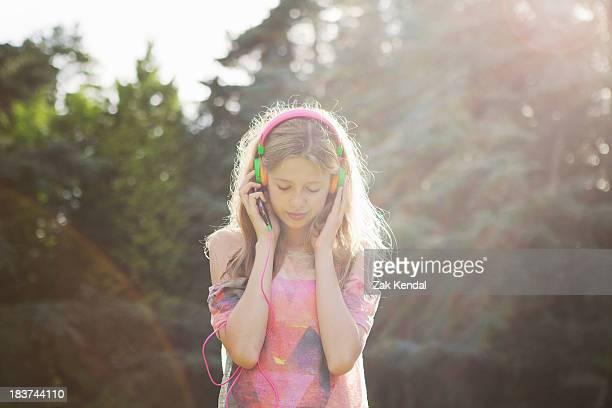 Teenage girl wearing headphones in sunlight