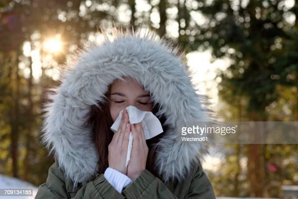 Teenage girl wearing hooded jacket blowing her nose in winter