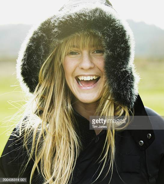 teenage girl (17-19) wearing hooded jacket, smiling, portrait - fur trim stock pictures, royalty-free photos & images