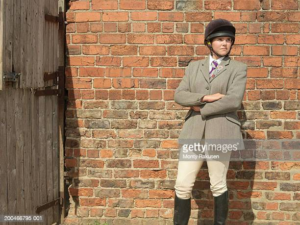 teenage girl (16-18) wearing horse riding helmet standing by stable - riding boot stock pictures, royalty-free photos & images